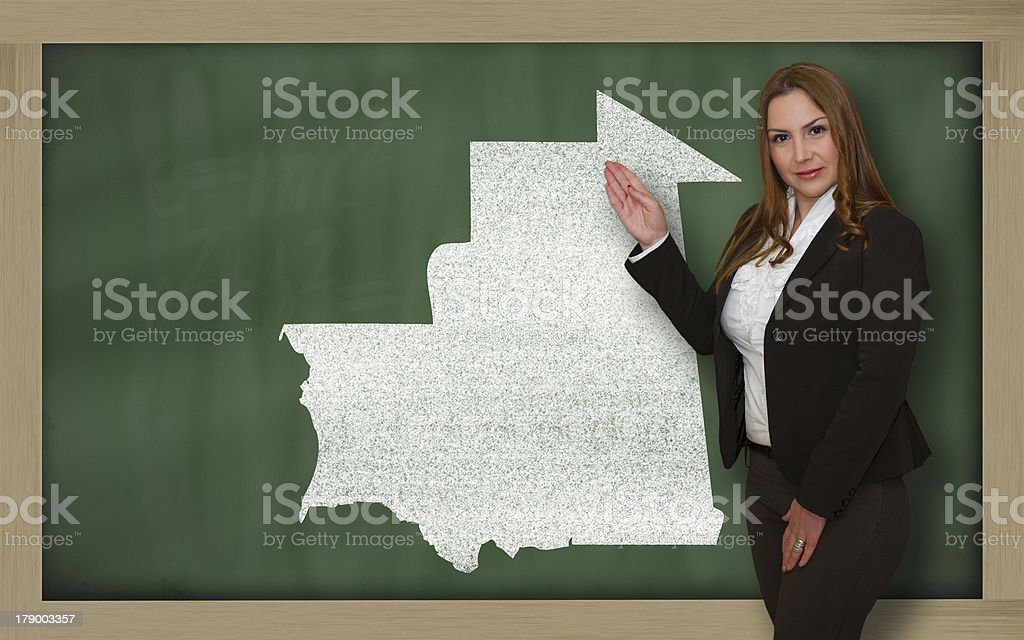 Teacher showing map of mauritania on blackboard stock photo
