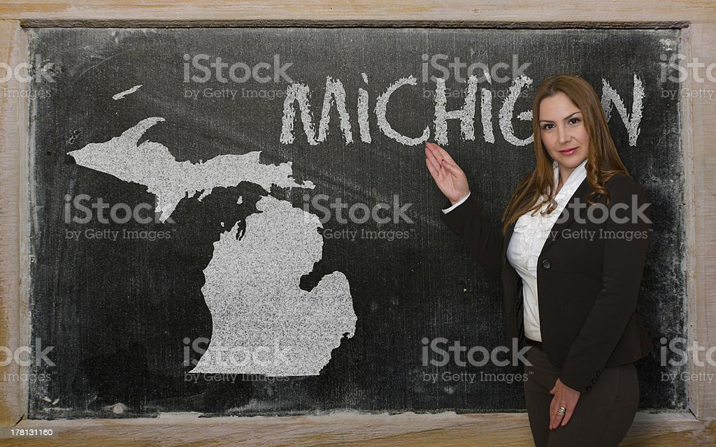 Teacher showing map of michigan on blackboard stock photo