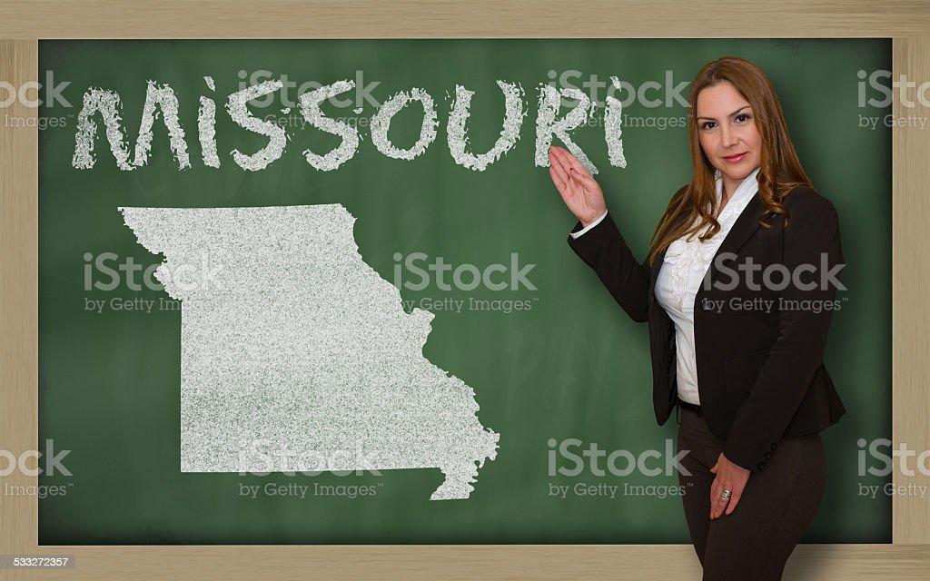 Teacher showing map of missouri on blackboard stock photo