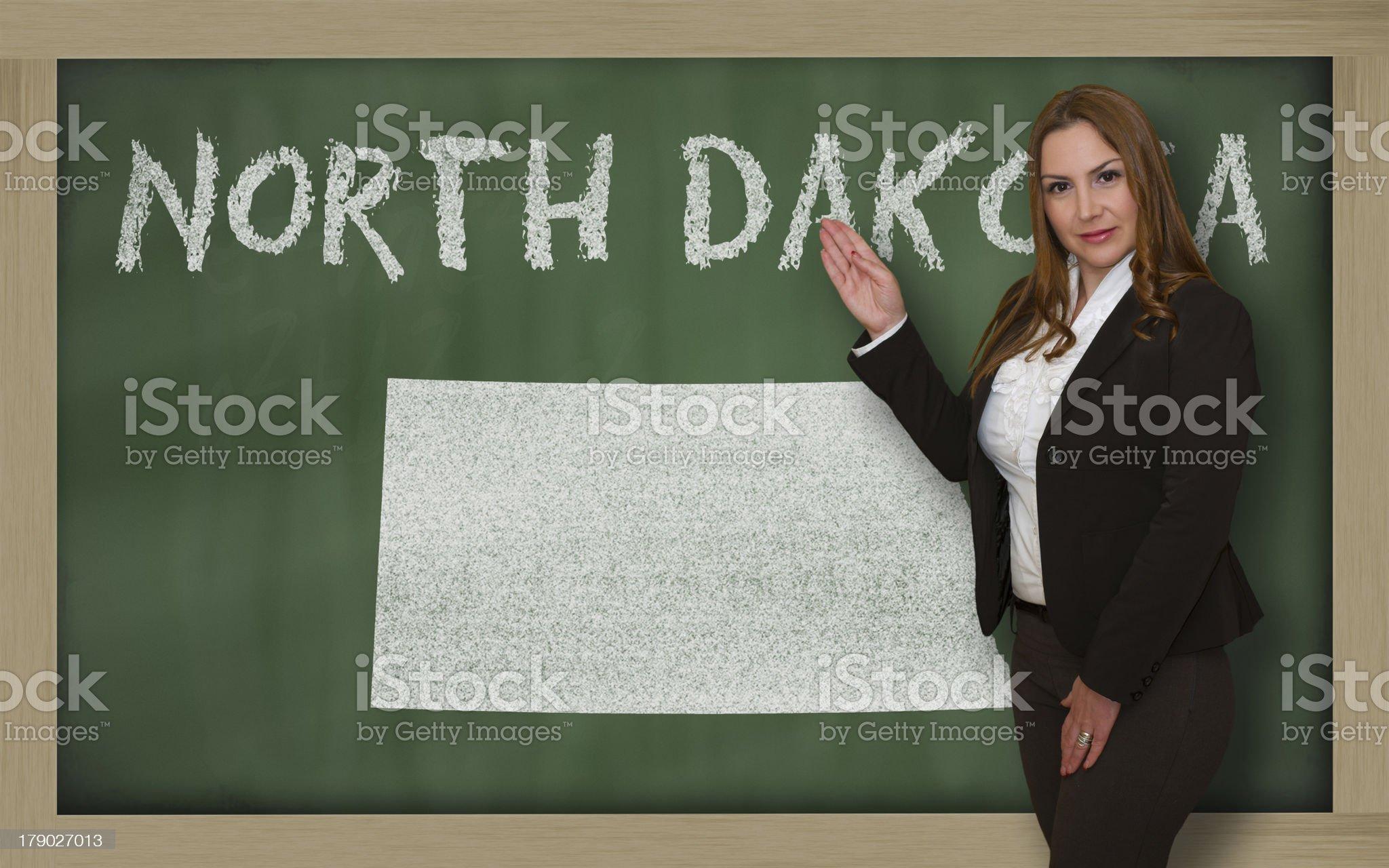 Teacher showing map of north dakota on blackboard royalty-free stock photo