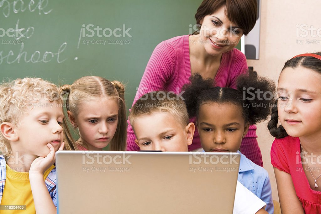 Teacher showing some cartoons to their students on the lap royalty-free stock photo