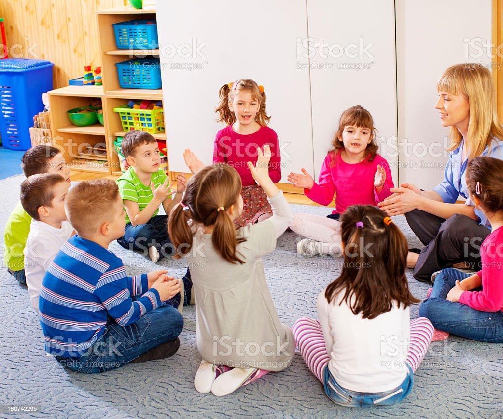 Teacher singing with children. stock photo