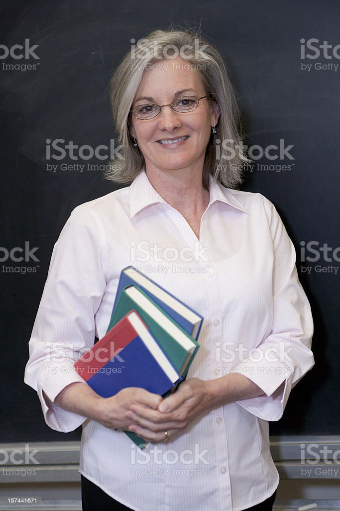 A teacher standing at the blackboard holding books royalty-free stock photo