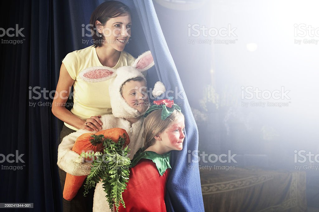 Teacher standing with children (5-7) in costumes behind stage curtain stock photo