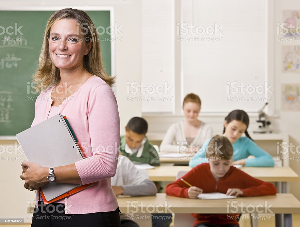 Teacher Standing with Notebook in Classroom stock photo