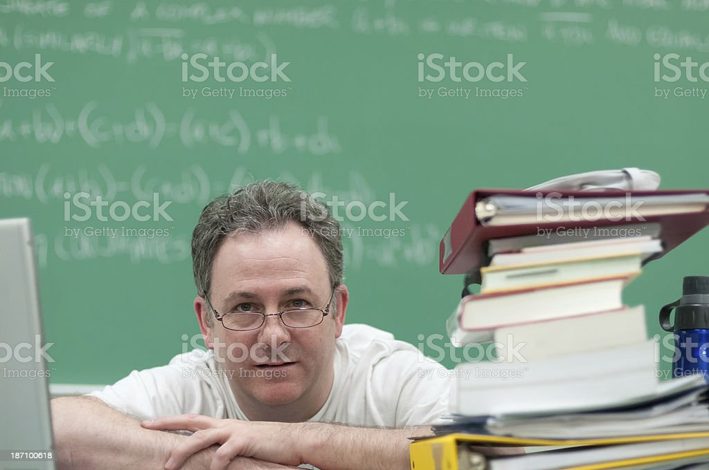 Teacher Surrounded by Laptop and Books Looks out at Class royalty-free stock photo