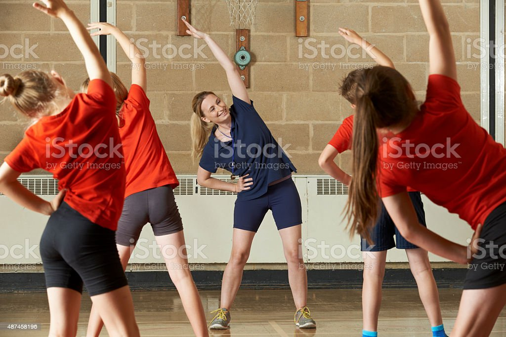 Teacher Taking Exercise Class In School Gym stock photo