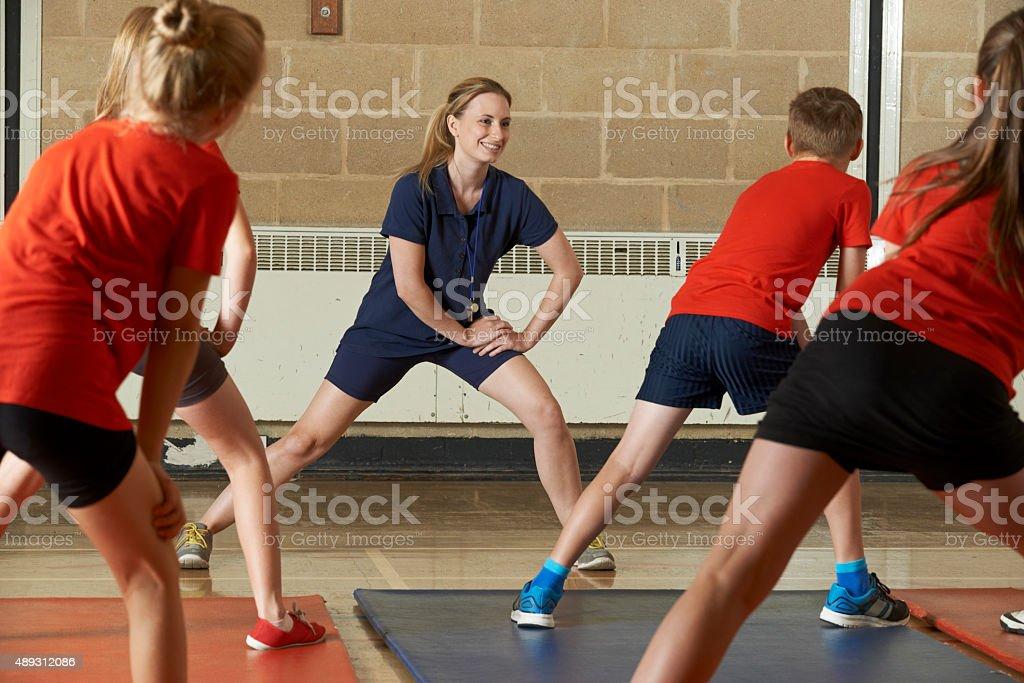 Teacher Taking Exercise Class In School Gym stock photo