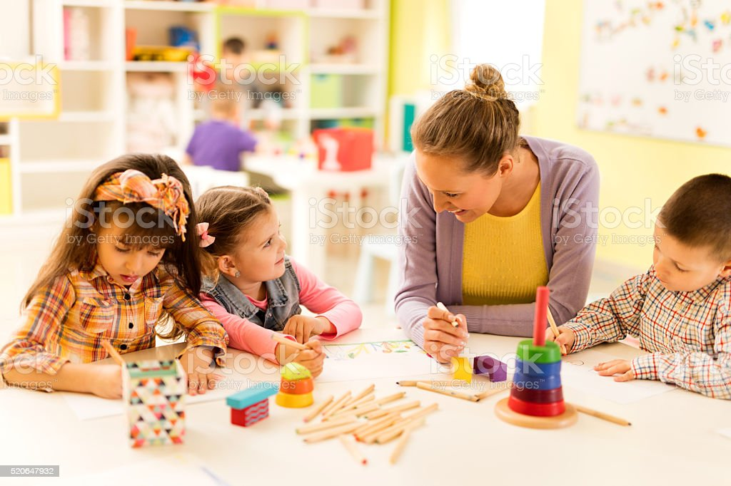 Teacher talking to little girl during art class in kindergarten. stock photo