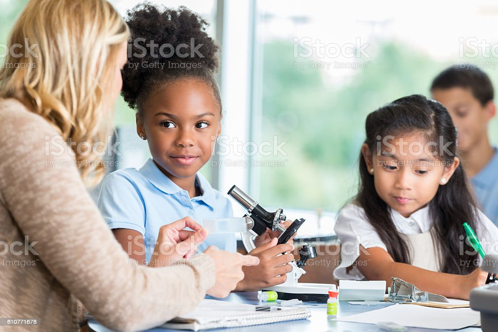 Teacher talks with elementary students about science assignment stock photo