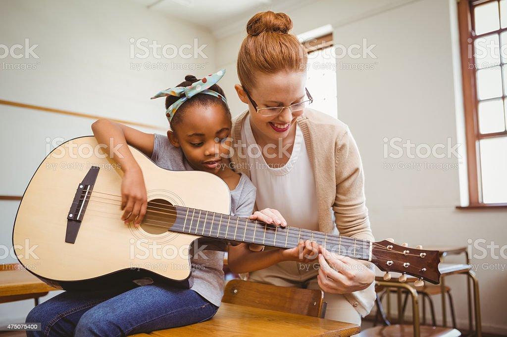 Teacher teaching girl to play guitar in classroom stock photo