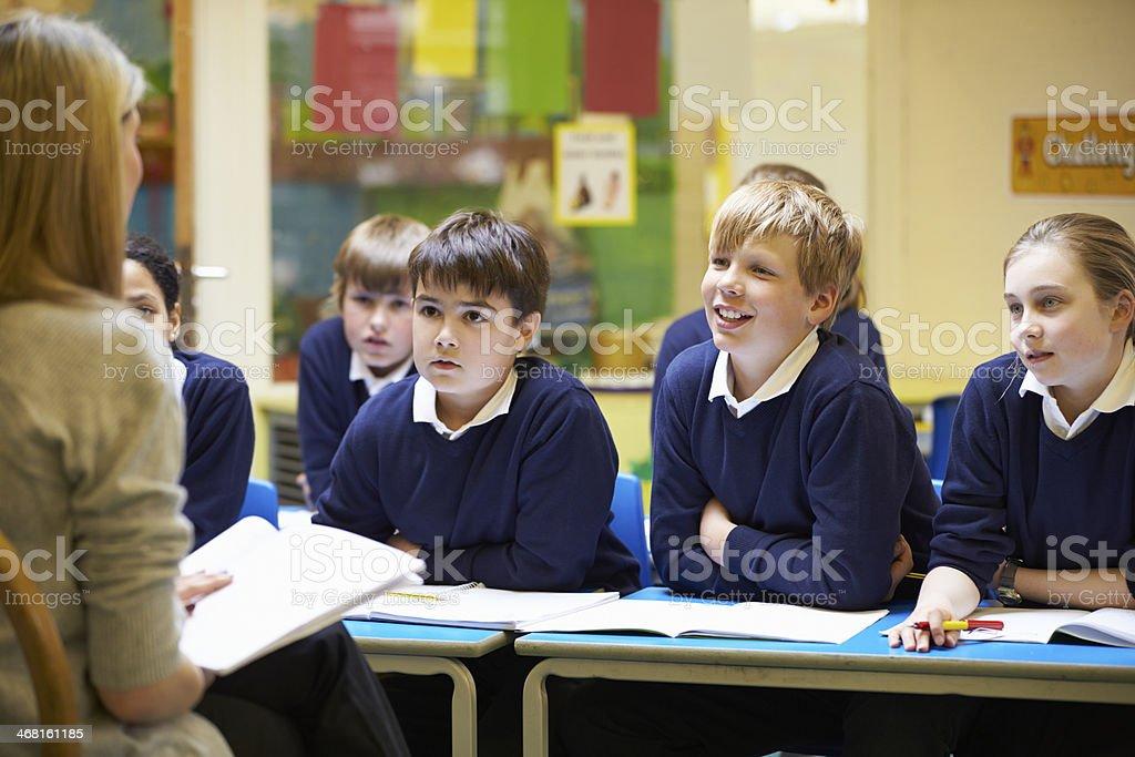 Teacher Teaching Lesson To Elementary School Pupils stock photo