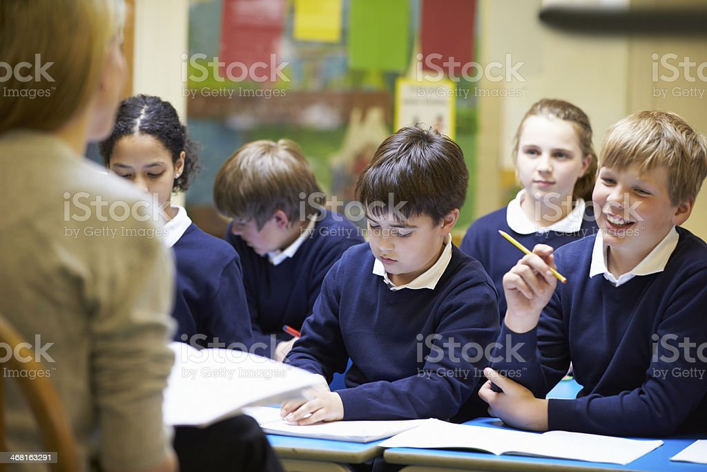 Teacher Teaching Lesson To Elementary School Pupils stock photo