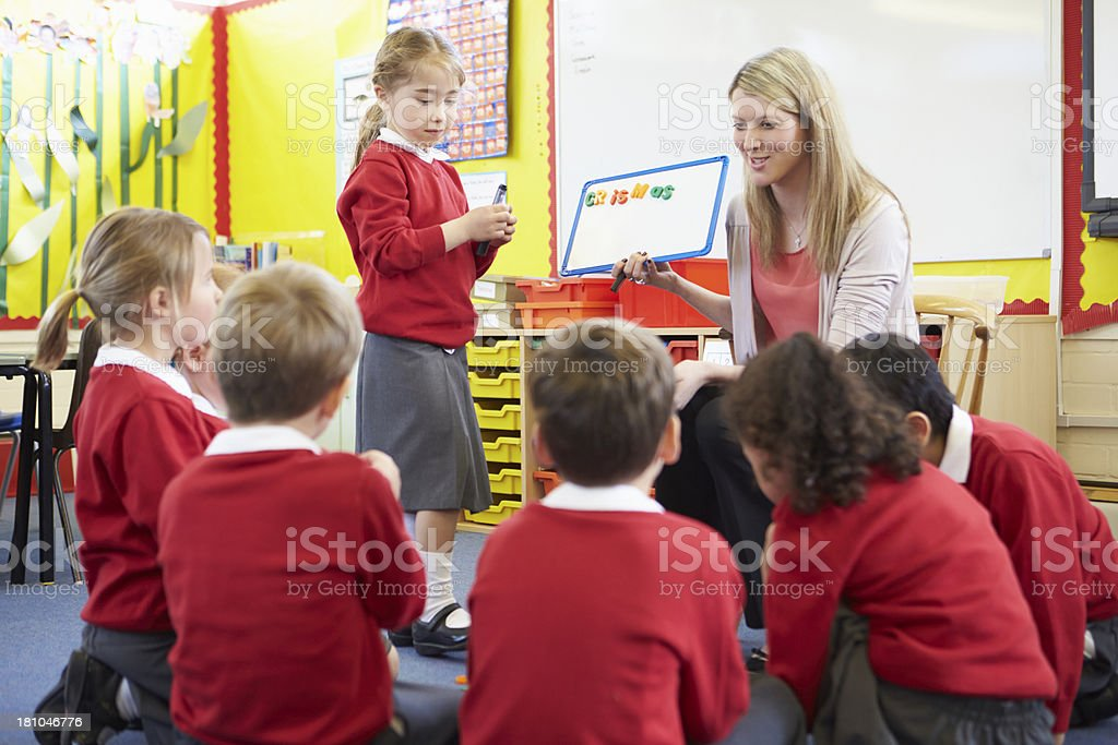 Teacher Teaching Spelling To Elementary School Pupils royalty-free stock photo