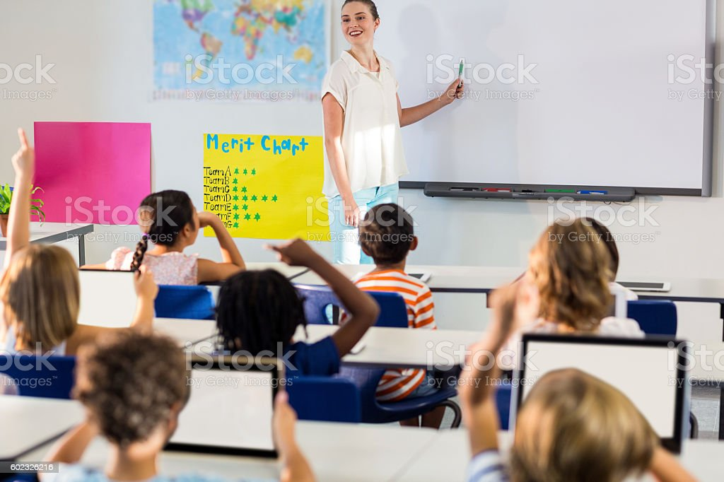 Teacher teaching students using whiteboard stock photo