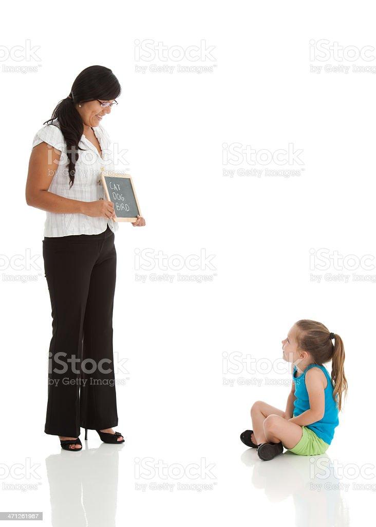 Teacher Teaching Young Girl To Read stock photo