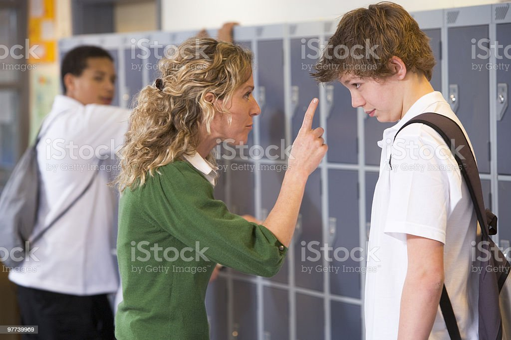 Teacher telling a student off royalty-free stock photo