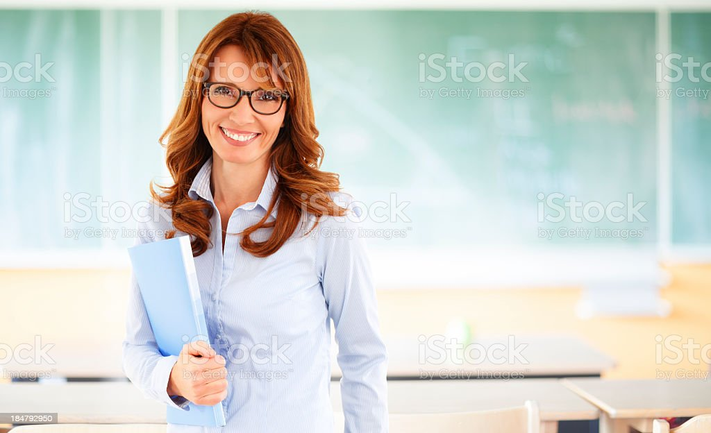 A teacher that is smiling while standing in the classroom  stock photo