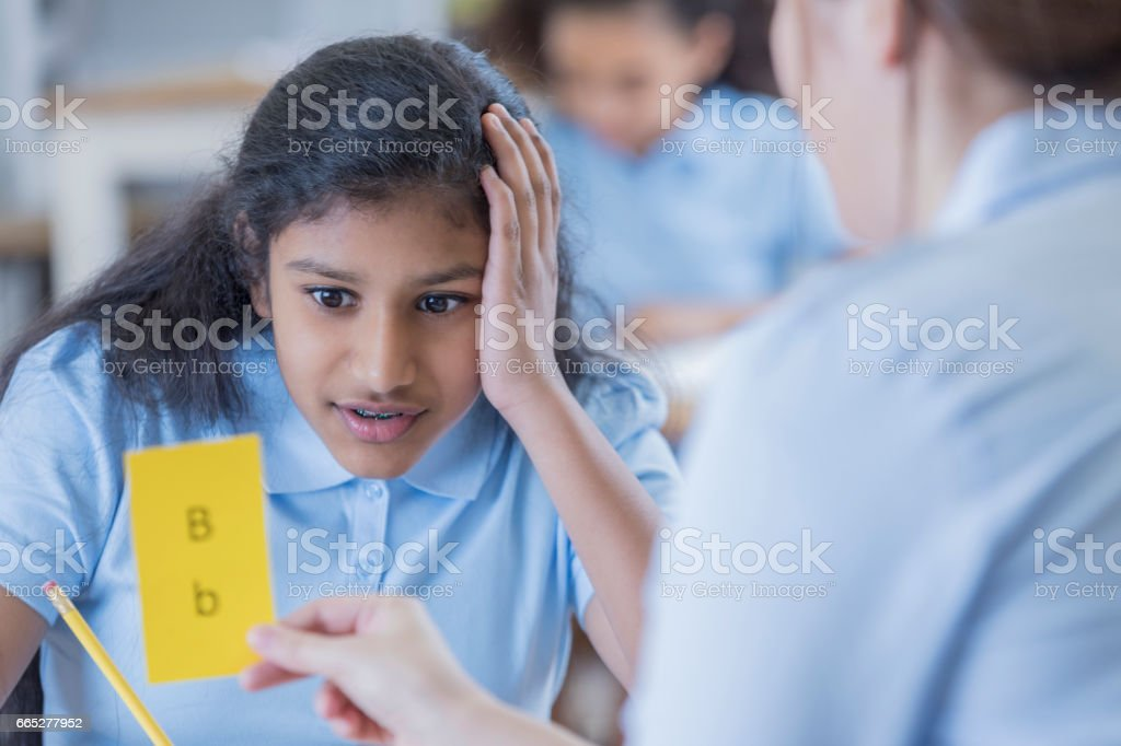 Teacher uses flashcards with female student stock photo