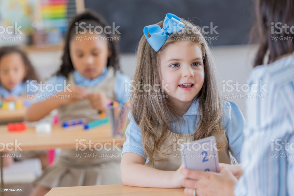 Teacher uses flashcards with young student stock photo