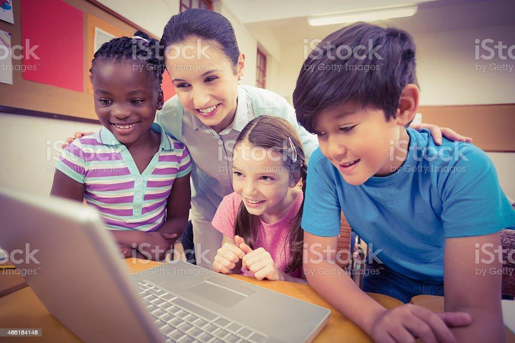 Teacher using laptop with pupils stock photo