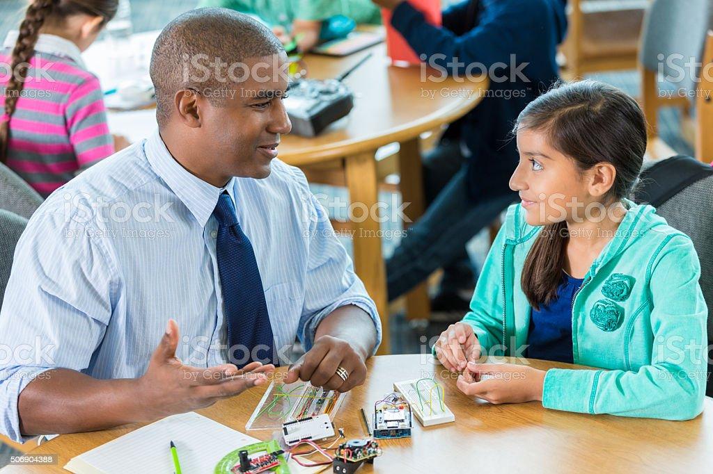 Teacher using robotics kit to teach Hispanic elementary science student stock photo