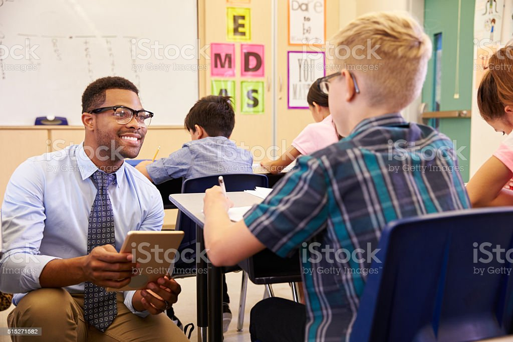 Teacher using tablet computer kneeling beside pupil's desk stock photo