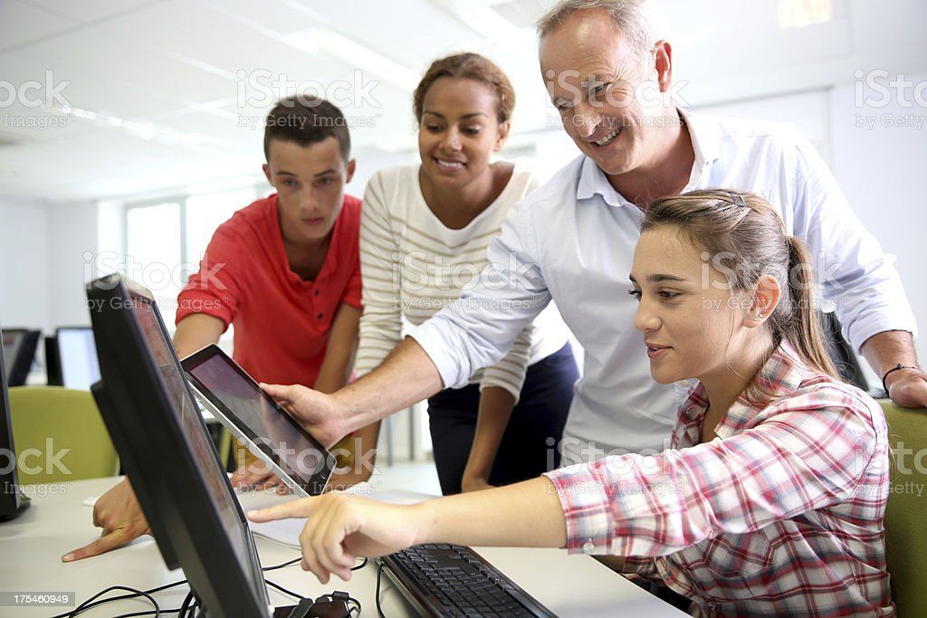 Teacher views screens in tech lab with students stock photo