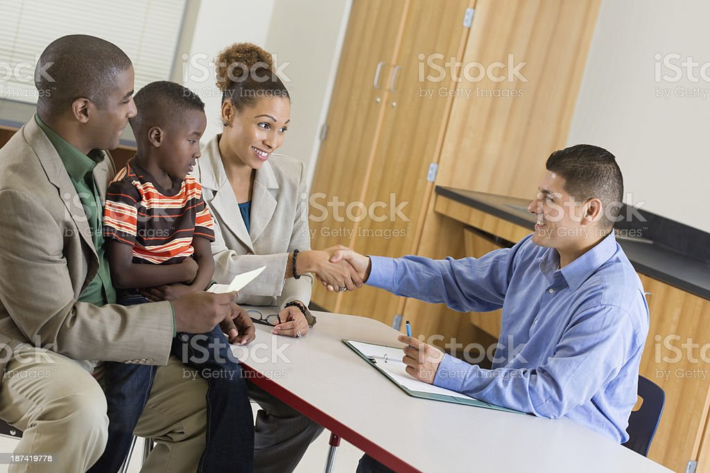 Teacher welcoming parents and student to school stock photo