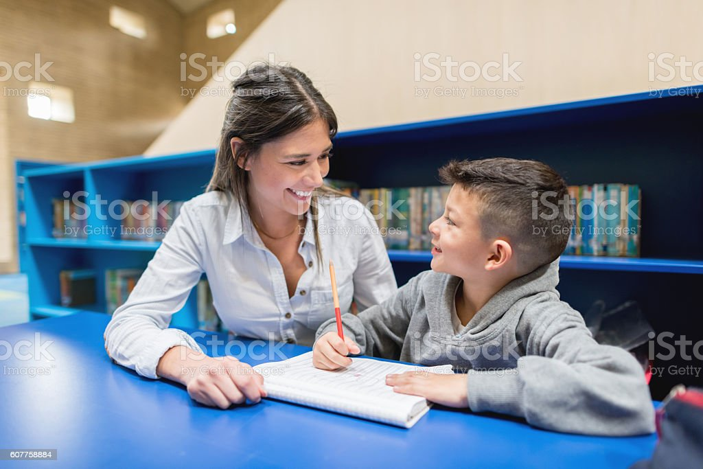 Teacher with a student at the library stock photo