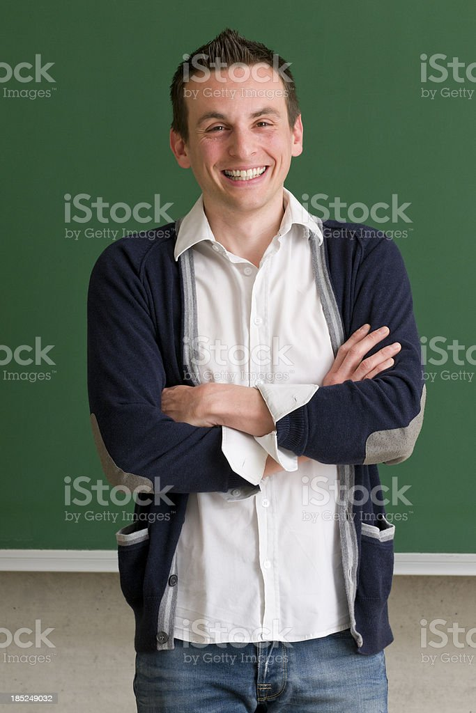 teacher with arms crossed at blackboard royalty-free stock photo