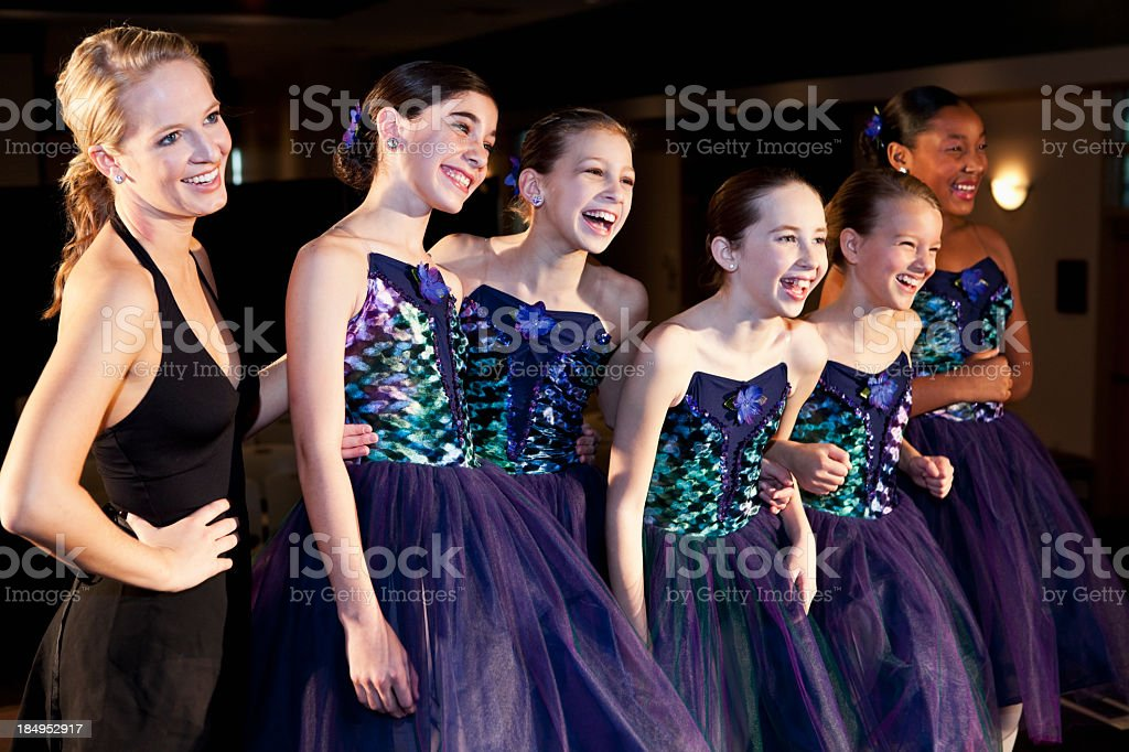 Teacher with ballet dancers in costume on stage stock photo