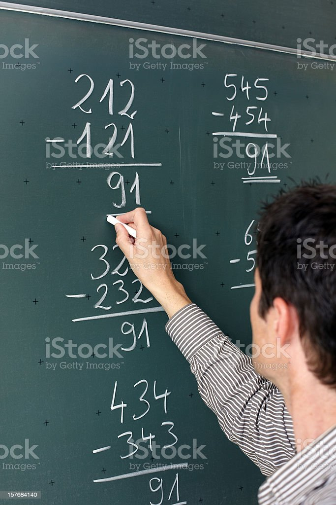 Teacher with chalk calculating on a black board stock photo