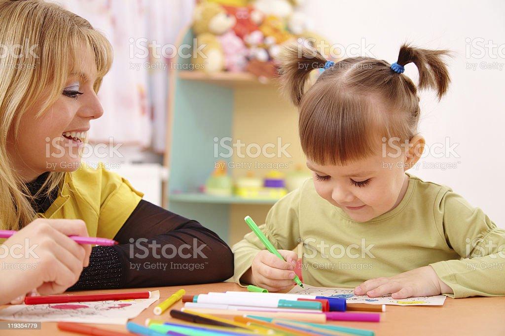 Teacher with child in preschool stock photo