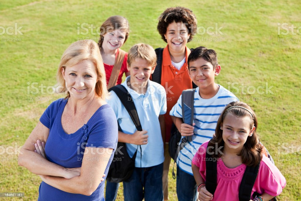 Teacher with  group of students outdoors stock photo