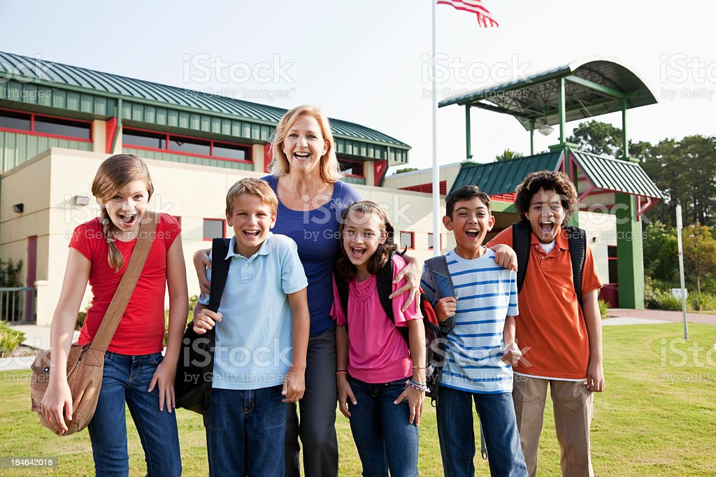 Teacher with  group of students outside school stock photo