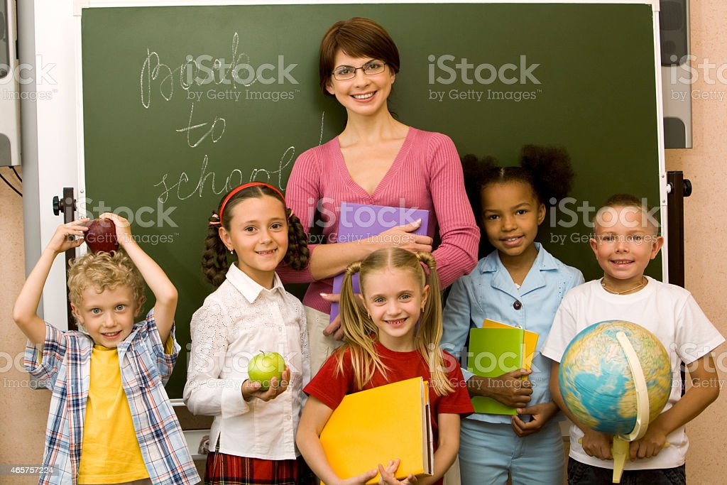 Teacher with her students in front of a blackboard stock photo