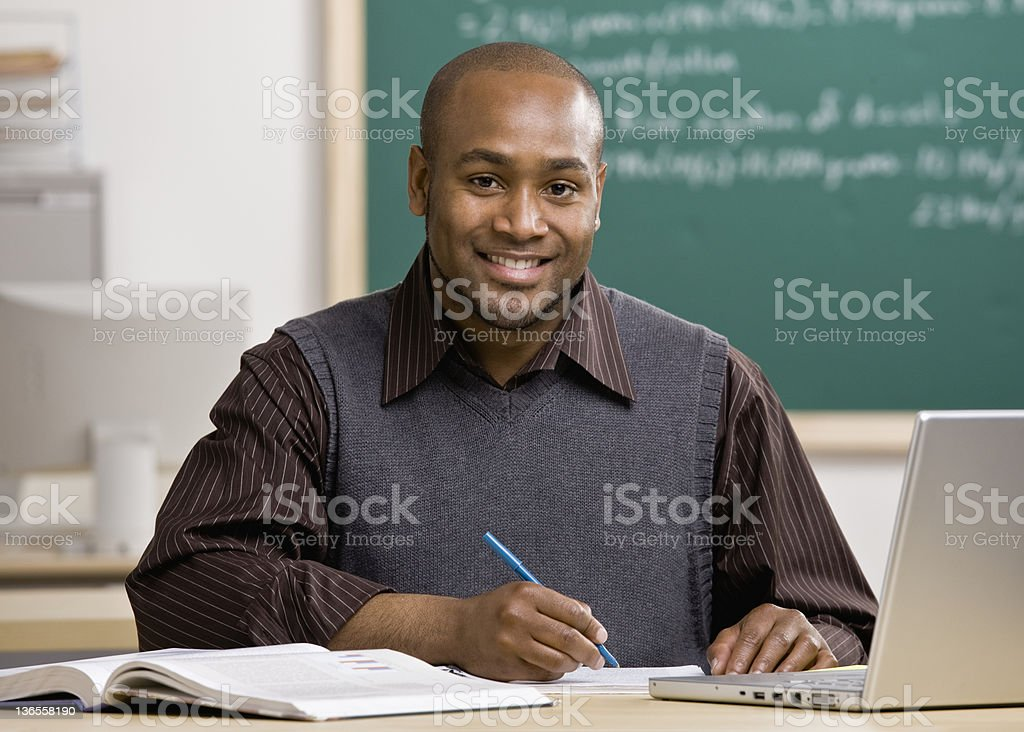 Teacher with laptop grading papers in school classroom stock photo