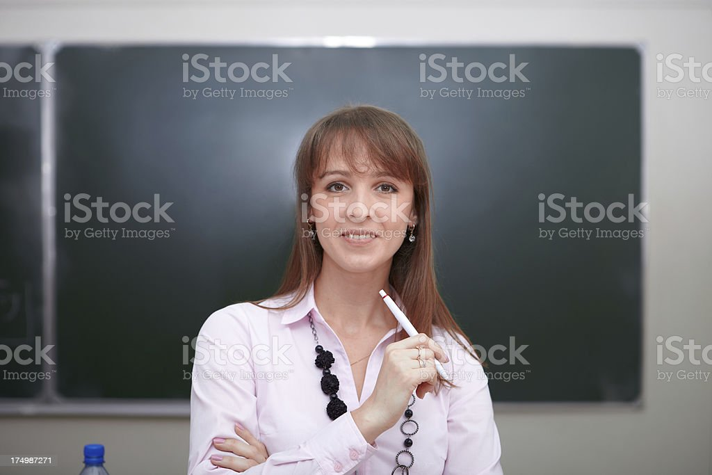 Teacher with pen in front of chalkboard. royalty-free stock photo