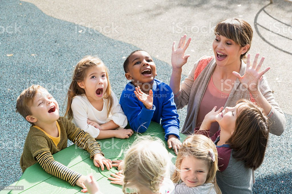 Teacher with preschool children having fun stock photo