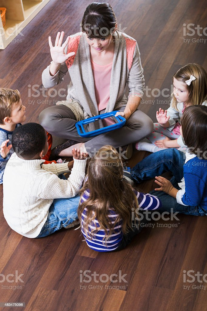 Teacher with preschoolers in class sitting on floor stock photo
