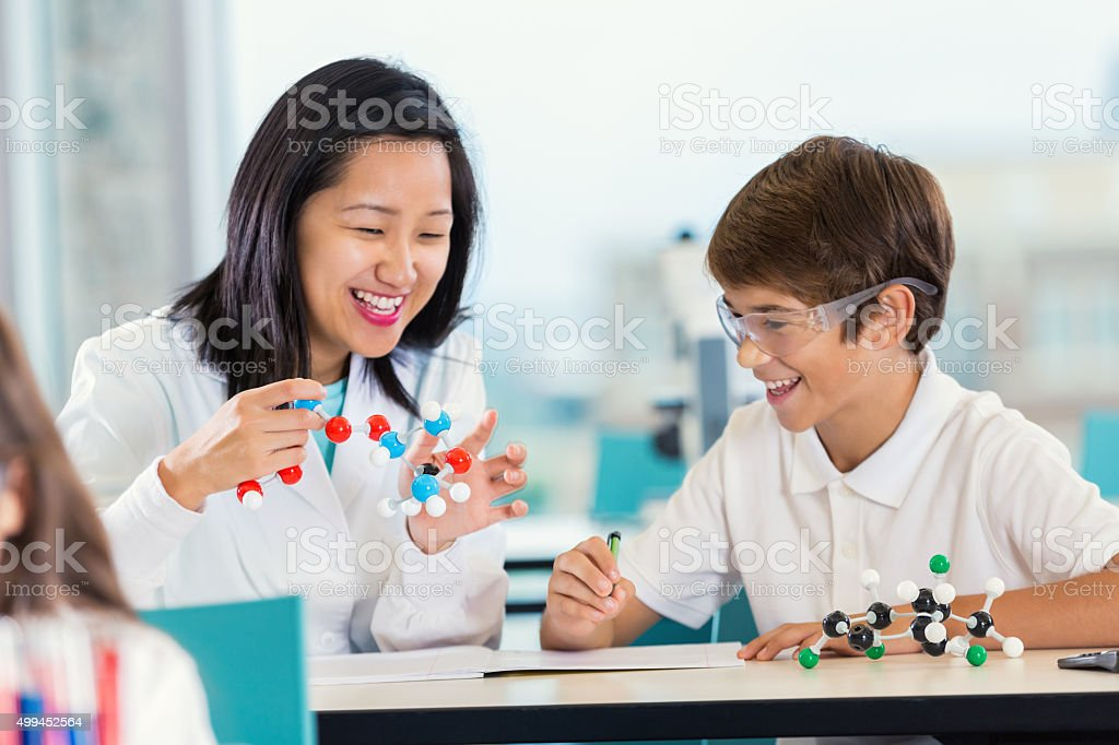 Teacher with preteen students teaching science class stock photo