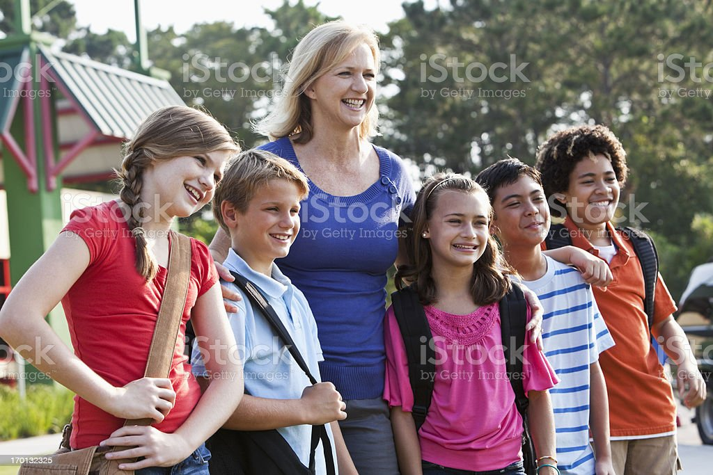 Teacher with students standing outside stock photo