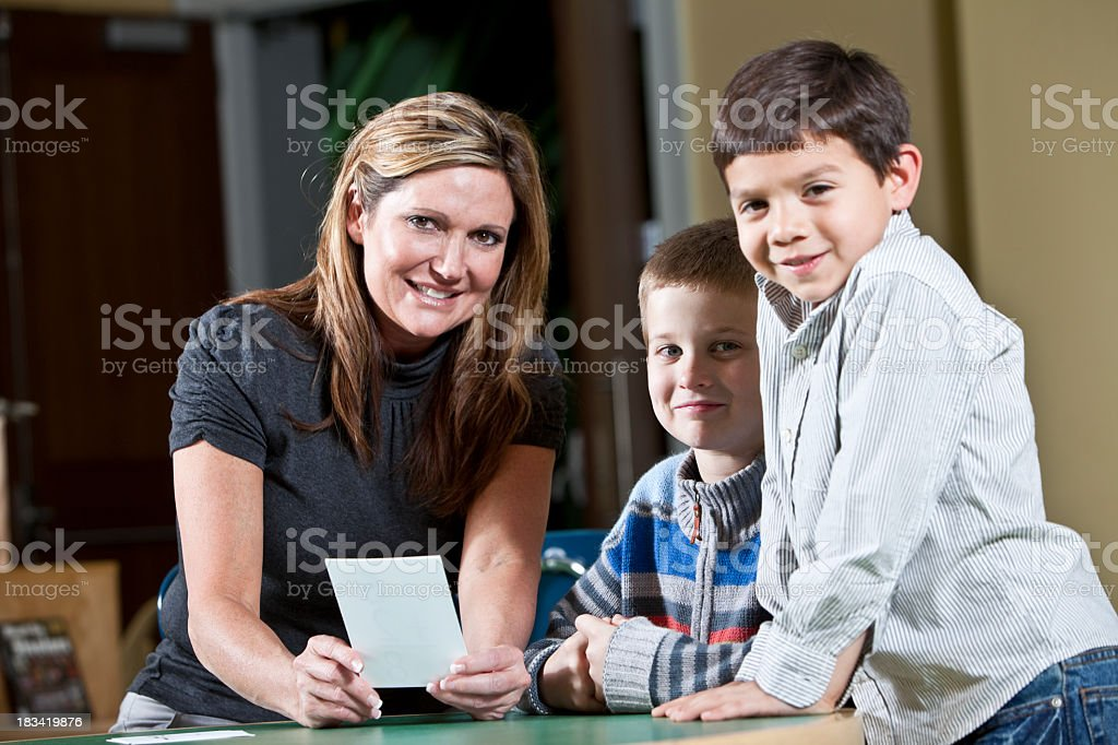 Teacher with two little boys stock photo