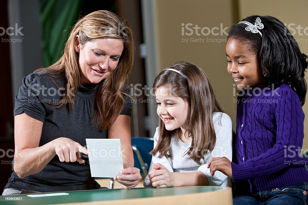 Teacher with two little girls stock photo