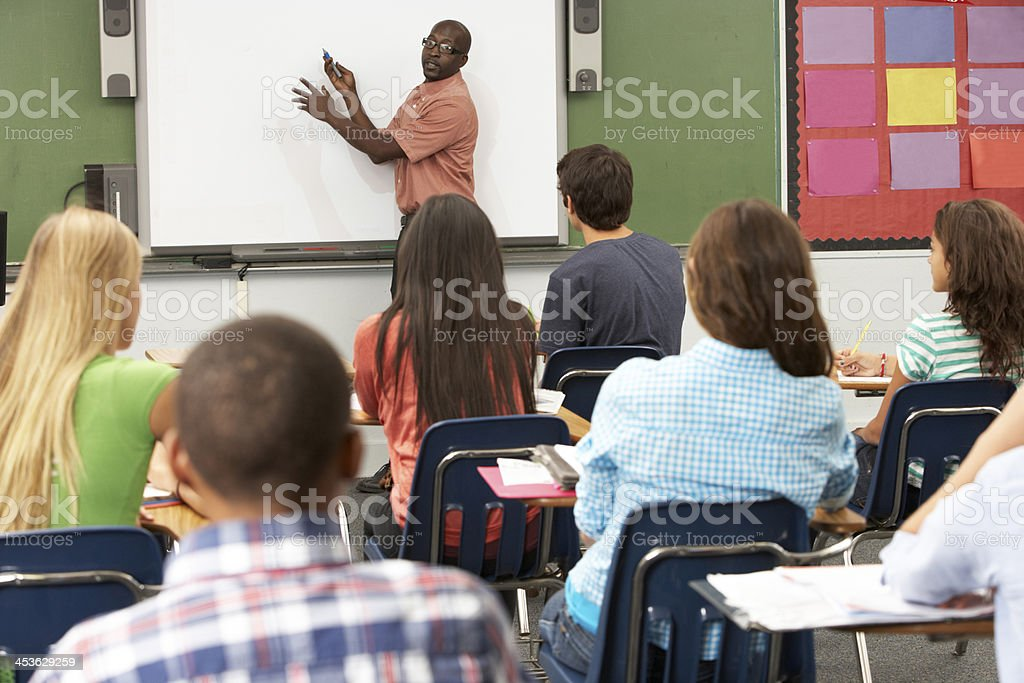 Teacher with whiteboard in front of class stock photo