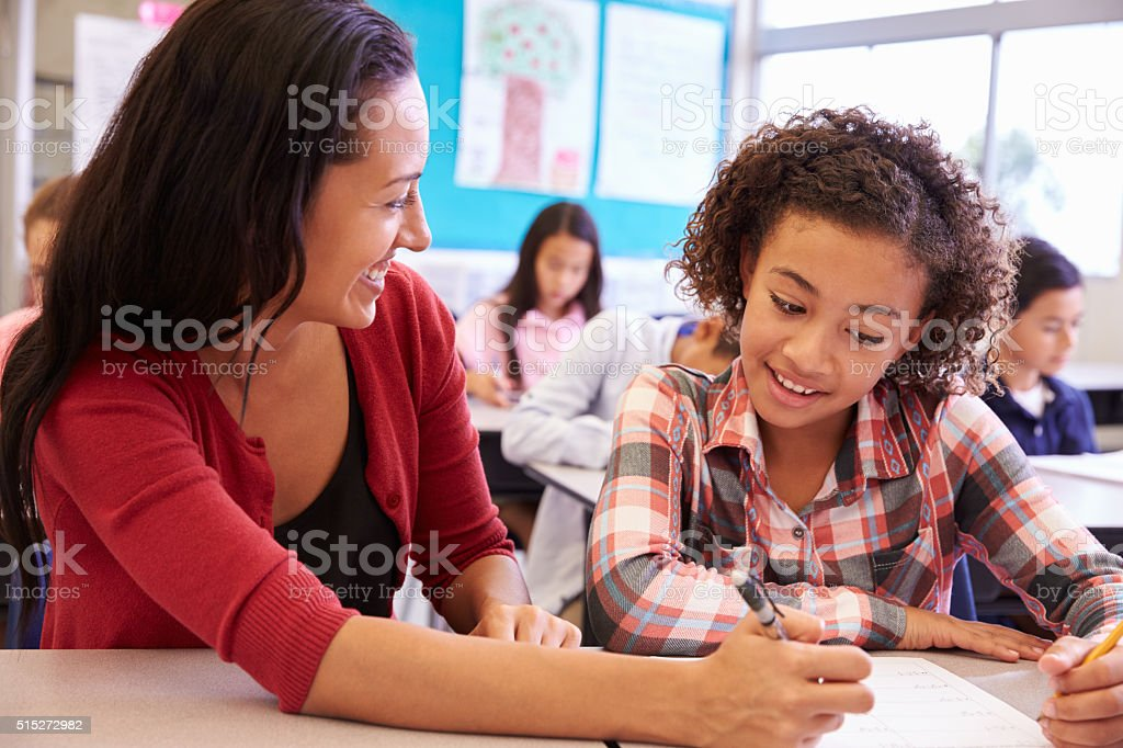 Teacher working with elementary school girl at her desk stock photo