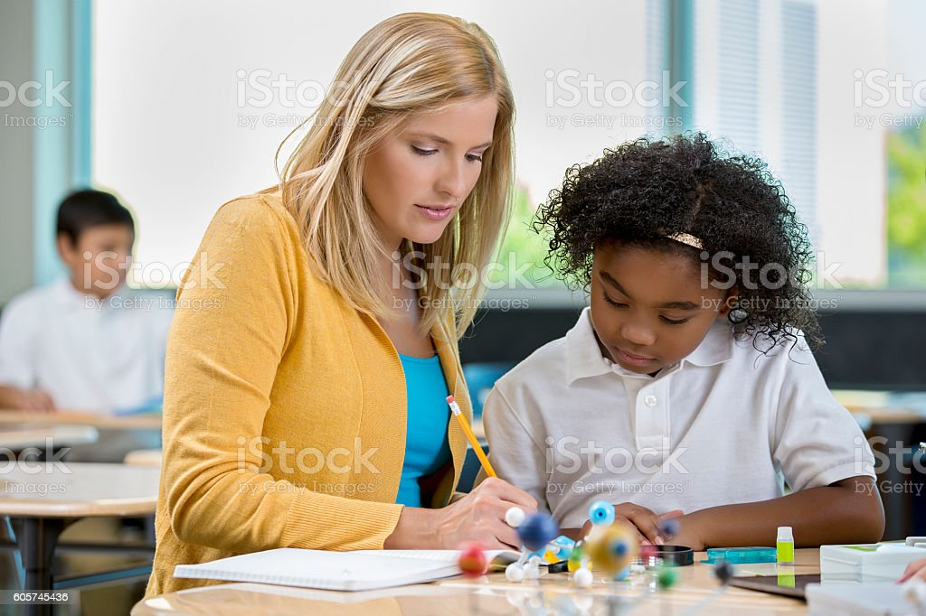 Teacher works with young student in science class stock photo