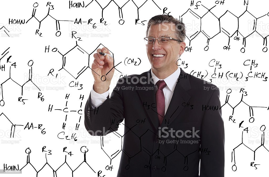 Teacher Writing a Chemistry Problem on the Board stock photo