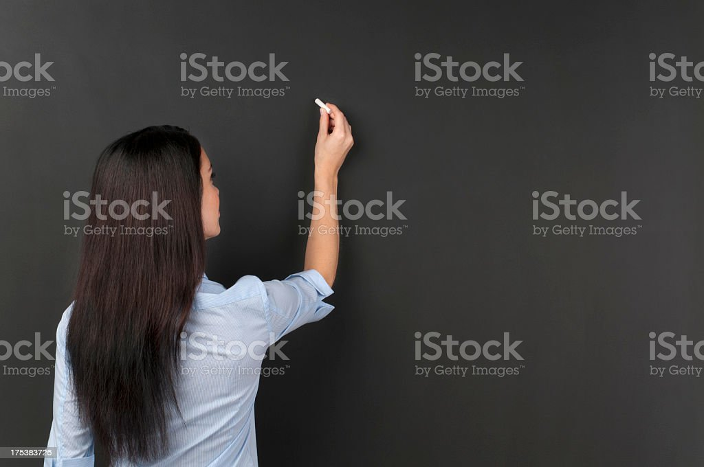 Teacher writing on a blackboard with chalk stock photo
